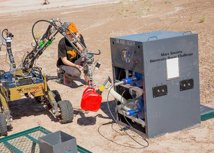 Rover pours fuel into a generator in Mars Society University Rover Challenge