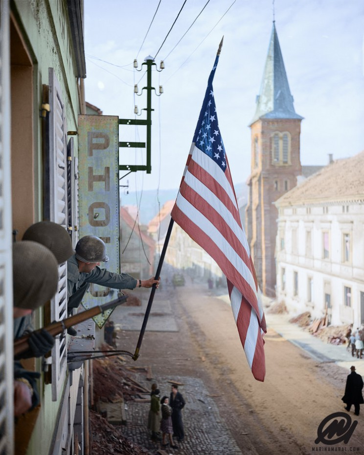 aptain Thomas H. Garahan, 'Easy' Company, 2nd Battalion, 398th Infantry Regiment, 100th Infantry Division Raises The 'Stars And Stripes' Flag Made Secretly By A Local French Girl.