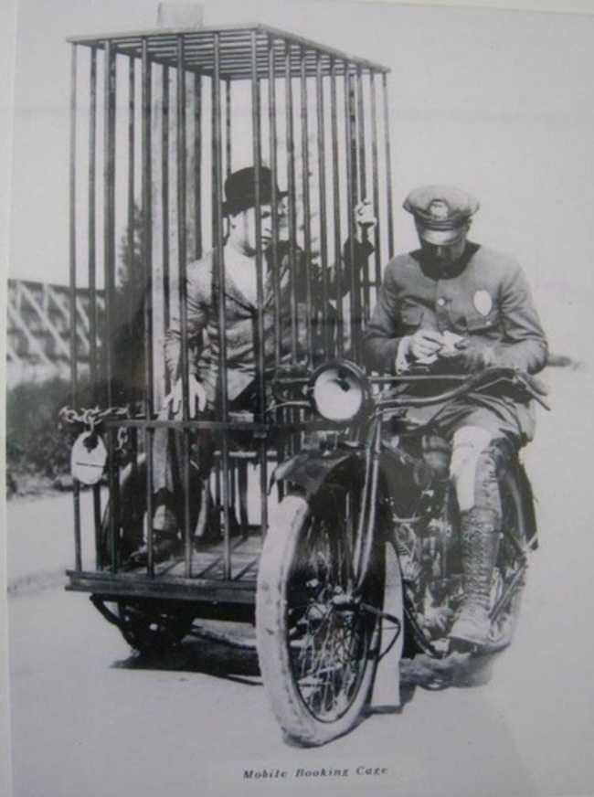 19. A police officer on a Harley and an old fashioned mobile holding cell. (1921)