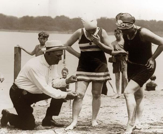 20. An beach official measures bathing suits to ensure they aren't too short (1920s)