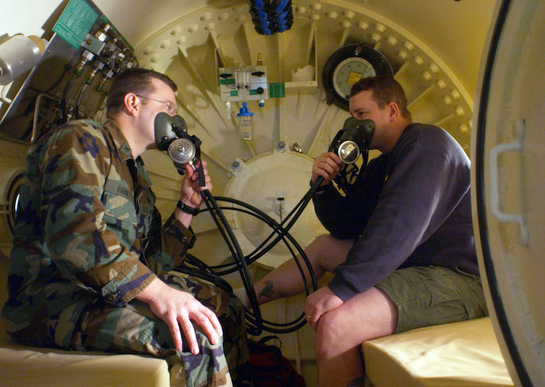 070208-N-8268B-001 Keyport, Wash. (Feb. 8, 2007) - Navy Diver 1st class Mike Barnett and Navy Diver 1st Class Chad Christensen test built-in breathing masks inside a recompression chamber located in the dive locker at Naval Undersea Warfare Center, Keyport. The recompression chamber is used to treat diving related disorders and other medical conditions with hyperbaric oxygen therapy (HBOT). U.S. Navy photo by Mass Communication Specialist Seaman Andrew Breese (RELEASED)