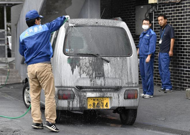 An officer of the city government cleans a car covered in volcanic ash which came from the eruptive crater of Mount Aso in Aso, Kumamoto prefecture, southwestern Japan, in this photo taken by Kyodo October 8, 2016. Mandatory credit Kyodo/via REUTERS