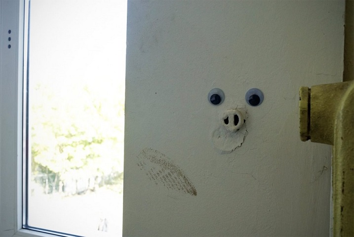 pipe sticking out of a wall with googly eyes