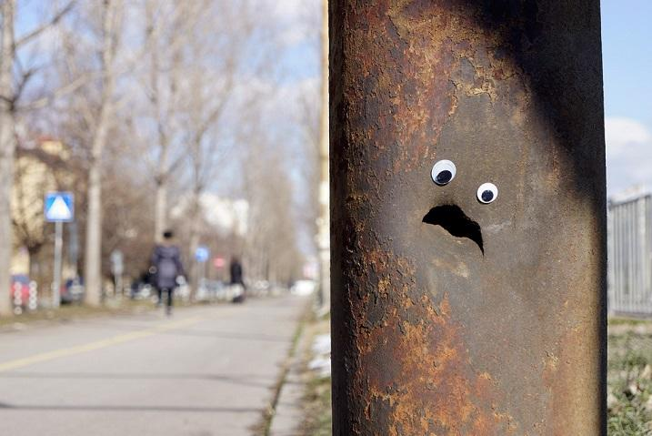 Corroding street post with googly eyes