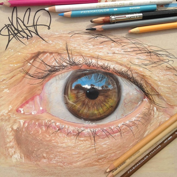 Photorealistic eyes drawn by artist using coloured pencils