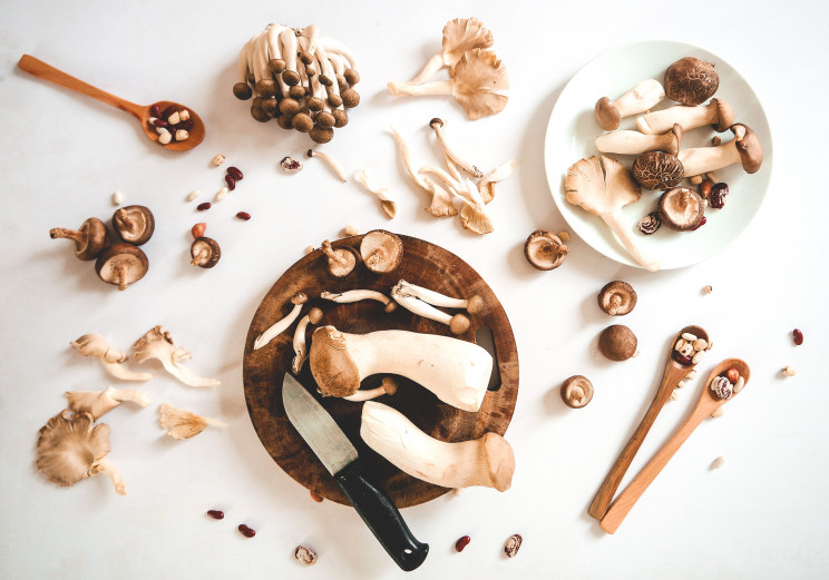 Various mushroom types set against a white background surrounding a wooden cutting board a knife with a black handle.