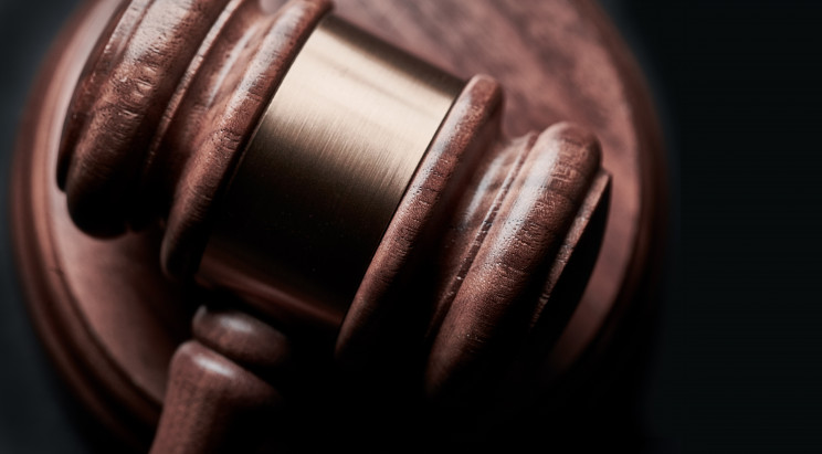 A closeup of a wooden gavel with golden metal band across its head resting on a platform.