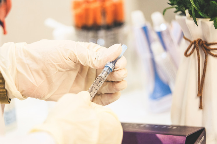 A doctor with white gloves pulls insulin out of a vial with a needle.