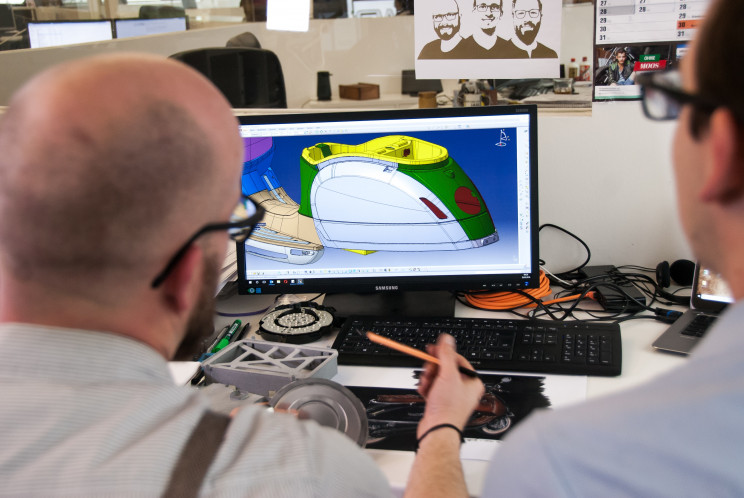 Two men use a computer-aided design program to analyze a machine part.