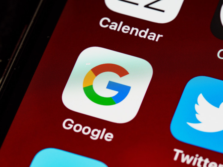 The Google app logo on a smartphone next to Twitter and other apps.