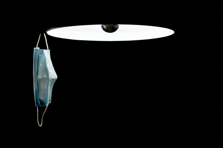 A COVID-19 mask hangs off of a lamp in a pitch black room.