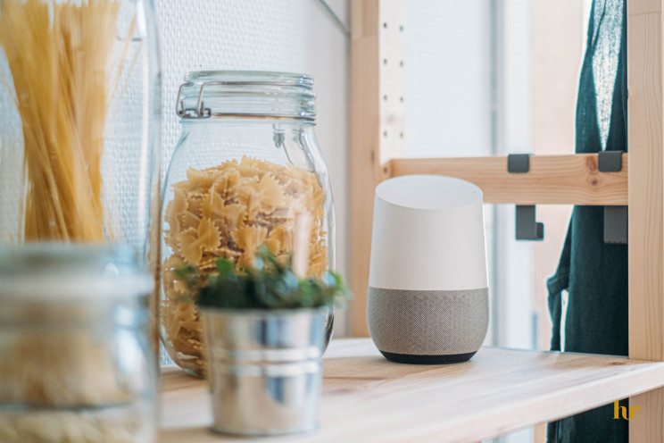 A Google Home smart speaker sits on a wooden shelf next to a jar filled with noodles in a kitchen.