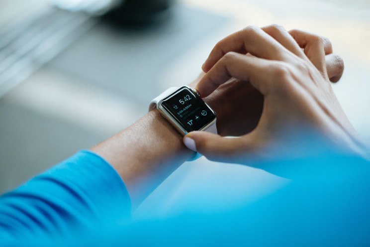 A person wearing a blue shirt operates their Apple Watch.