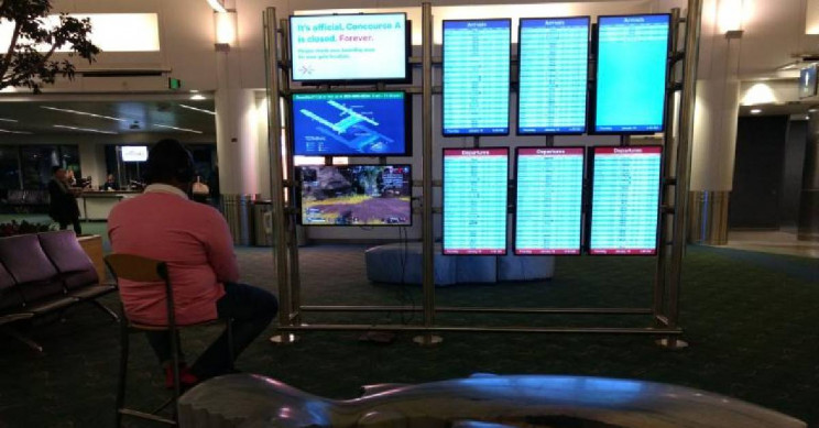 Passenger waiting for flight takes over airport screen to play video games