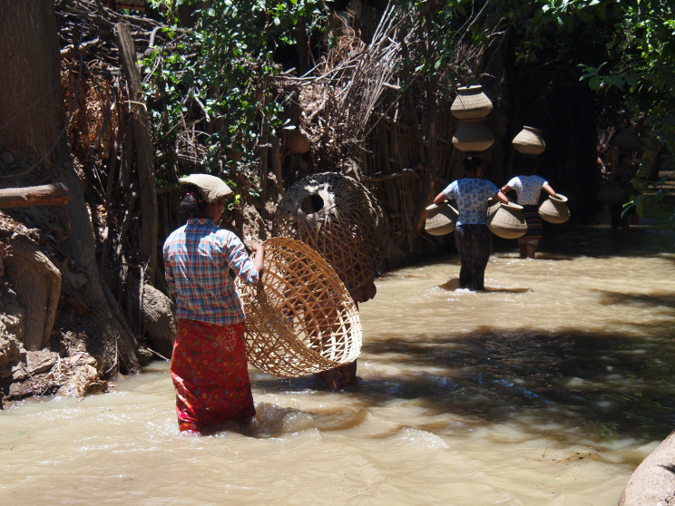 Three people carrying baskets and vases wade through knee-deep floodwaters in Myanmar.