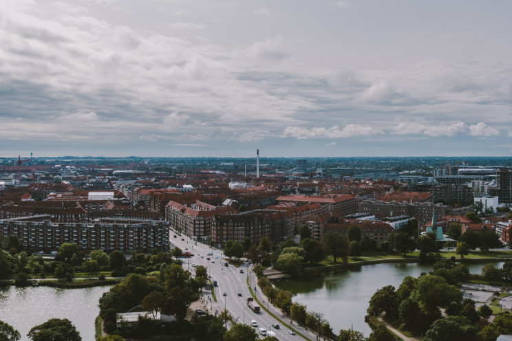 Copenhagen from a nearby hillside, red, tiled-roof buildings and a bridge stretch into the distance under a grey sky.