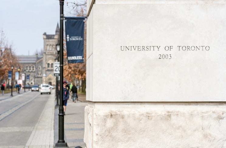 Toronto, Canada - A stone sign for the University of Toronto, at one of the university's Downtown Campus locations, with traffic and pedestrians in the background.