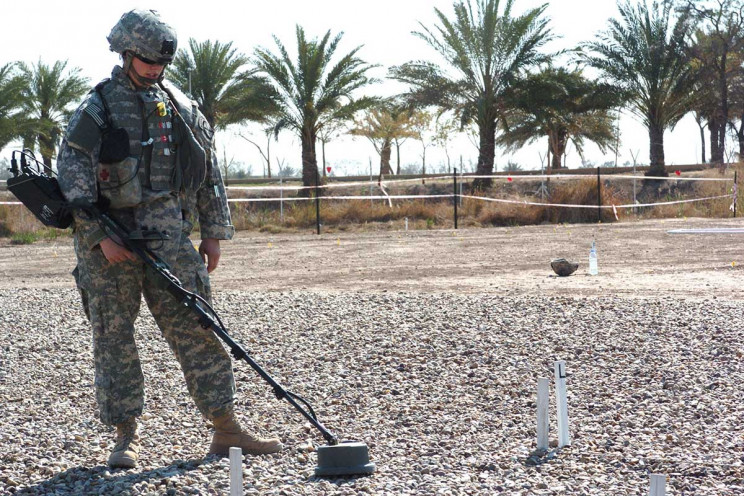 Soldier searches for landmine